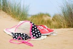 Bikiní, sombrero del sol y zapatos en la playa Fotografía de archivo