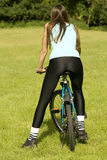 Biking. Fitness woman on a bike, shot from back Stock Photos