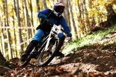 Biking as extreme and fun sport. Downhill biking. Biker jumps. Stock Photo