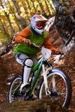 Biking as extreme and fun sport. Downhill biking. Biker jumps. Stock Photography