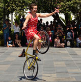 Biking Busker. A female busker riding a bicycle Stock Photography