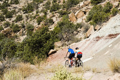 Biking in Colorado Nat Monument. Two bikers ride through the sandstone scenery along the Rim Rock Drive in Colorado National Park Stock Images