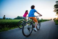 Biking da menina e do menino Fotografia de Stock Royalty Free