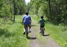 Biking del figlio e del papà Fotografia Stock