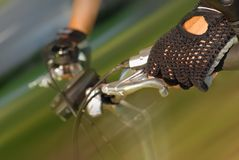 Biking detail. Hands of a bicyclist speeding down the road.  Motion blur with sharp focus on the hand on right Stock Photos