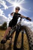 Biking e luz do sol da montanha da mulher Fotos de Stock Royalty Free
