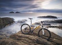 Biking e rocha da montanha na costa de mar Imagem de Stock