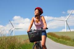 Biking entre turbinas de vento Imagem de Stock Royalty Free