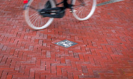 Biking in Europe. A cyclist passes a bike sign in the bike lane path, Amsterdam, Holland Royalty Free Stock Photo