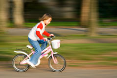 Biking fast. Motion blur of a kid biking fast in the park royalty free stock photography