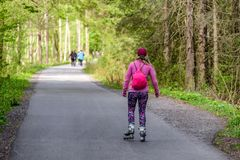 Biking in forest. Skating on roller blades in spring forest at asphalt road. Gaderska valley in Slovakia royalty free stock image
