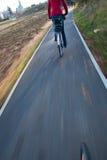 Biking - giovane donna che biking per funzionare Fotografia Stock Libera da Diritti