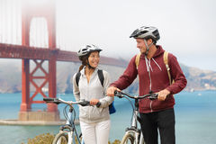 Biking Golden Gate Bridge - couple sightseeing. In San Francisco, USA on bicycle. Young couple tourists on bike tour enjoying the view at the famous travel Stock Photography