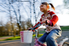 Biking happy. Motion blur of a little girl biking in the park stock image