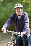 Biking maggiore dell'asiatico Immagini Stock