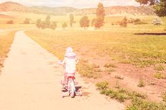 Biking. Toddler learning how to ride her first bike Royalty Free Stock Image