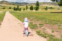Biking. Toddler learning how to ride her first bike Stock Image