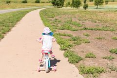 Biking. Toddler learning how to ride her first bike Royalty Free Stock Images