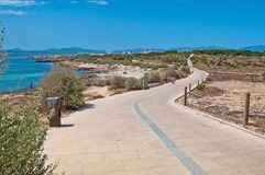Cloud patterns on blue summer skies. Biking track across coastal landscape with azure water on a sunny summer day in Mallorca, Spain royalty free stock image
