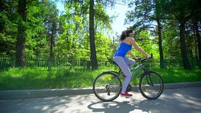 Biking woman cycling on bike. Sporty woman riding bicycle in summer day. Female cyclist outdoor activity living healthy. Lifestyle. summer time. slow-motion stock footage