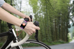 Biking woman hands wearing health sensor smart watch Stock Photo