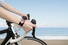 Biking woman hands wearing health sensor smart watch Royalty Free Stock Photo