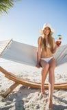 Bikini alegre y sunhat que llevan rubios que se sientan en ingenio de la hamaca imágenes de archivo libres de regalías