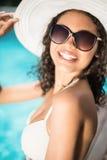 Bikini blanco que lleva y sombrero de la mujer hermosa que se sientan cerca de piscina Fotos de archivo