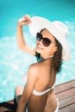 Bikini blanco que lleva y sombrero de la mujer hermosa que se sientan cerca de piscina Fotos de archivo libres de regalías
