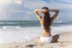 Bikini blanco que se sienta de la muchacha atractiva de la mujer en la playa Imagenes de archivo