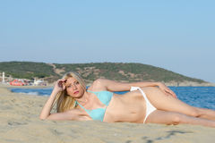 Bikini blond d'usage de femme se trouvant sur le sable Photo stock
