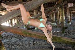 Bikini blond unter einem Pier Lizenzfreie Stockbilder