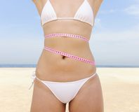 Bikini body: Woman with measure tape Royalty Free Stock Photo