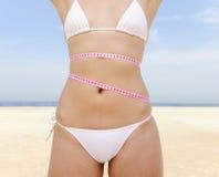 Bikini body: Woman with measure tape royalty free stock photo