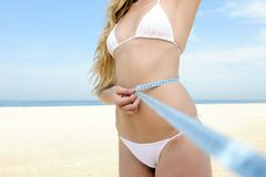 Bikini body: Woman measuring her waist Stock Image