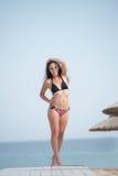 Bikini bonito del desgaste de la muchacha que se coloca en una trayectoria de madera en la arena Imagen de archivo