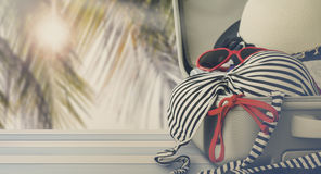 Bikini and clothes in luggage on wooden. Vintage style Royalty Free Stock Image