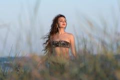 Bikini d'usage de femme, pose parmi des usines d'arénaire d'ammophila sur le premier plan Photos stock