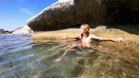 Bikini d'uso dell'arcobaleno della giovane donna snella che gode del mare e del sole sulla spiaggia Mediterranea stock footage