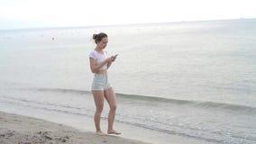 Bikini d'uso della ragazza del Sunbather facendo uso di uno Smart Phone sulle vacanze estive sulla spiaggia stock footage