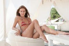 Bikini de port de dame blonde mince sportive entouré par des tissus photo stock