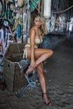 Bikini de port modèle et bijoux de maillot de bain blond sexy posant assez devant le fond de graffiti Image libre de droits
