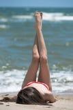Bikini delgado del desgaste de la muchacha, mintiendo en una playa arenosa y una manera de elevación encima de sus piernas Fotografía de archivo