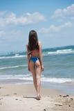 Bikini delgado del desgaste de la muchacha, playa con las ondas salvajes Foto de archivo libre de regalías