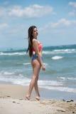 Bikini delgado del desgaste de la muchacha, playa con las ondas salvajes Imágenes de archivo libres de regalías