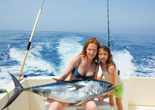 Bikini fisher woman and daughter with bluefin tuna. Bikini fisher women and daughter girl holding big bluefin tuna catch on boat deck royalty free stock photography