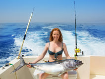 Bikini fisher woman holding bluefin tuna on boat. Beautiful bikini fisher woman holding big bluefin tuna catch on boat deck Royalty Free Stock Photo