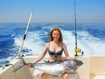 Bikini fisher woman holding bluefin tuna on boat. Beautiful bikini fisher woman holding big bluefin tuna catch on boat deck royalty free stock photo