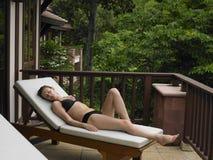 Bikini-Frau, die auf Deckchair stützt Lizenzfreie Stockbilder