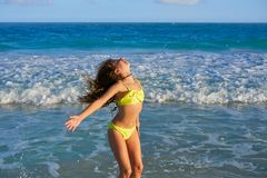 Bikini girl jumping in Caribbean sunset beach. Bikini teen girl jumping happyt in Caribbean sunset beach splashing shore stock images